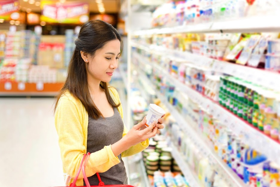 Asian woman buys in the supermarket yogurt